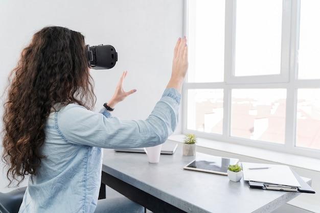 Женщина с помощью гарнитуры виртуальной реальности