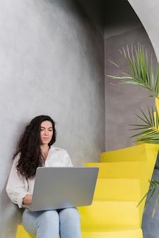 Женщина работает и сидит на лестнице