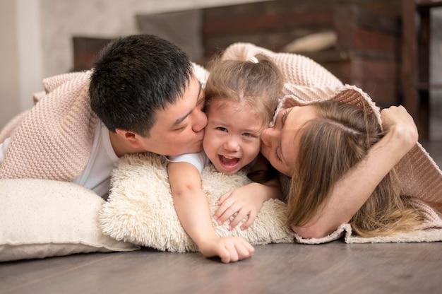 Родители целуют девушку