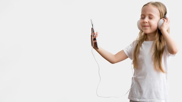 Девушка слушает музыку на мобильном телефоне с наушниками