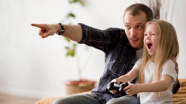 ジョイスティックでゲームをプレイする父を持つ少女