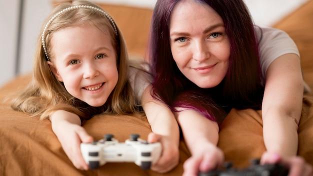 小さな女の子とジョイスティックで遊んでママ