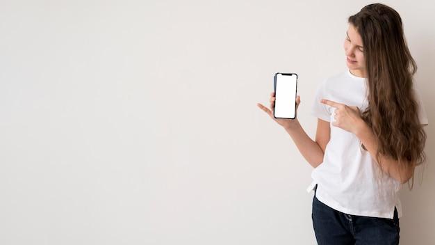 Копия пространство девушка, указывая на мобильный