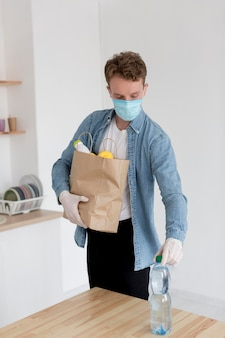 食料品の袋を持つ男