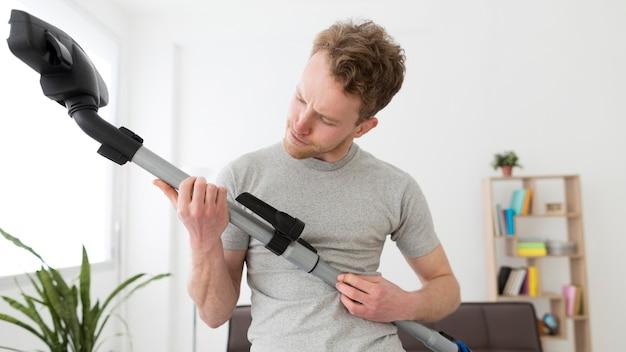 家の掃除機を持つ男
