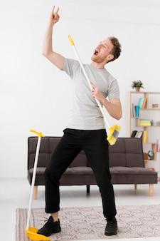 Мужчина поет на метле во время уборки