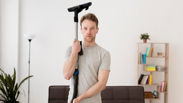 Вид спереди человек с пылесосом