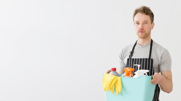 Человек с моющими средствами в корзине