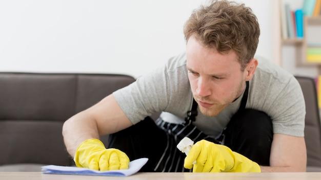 Человек, чистящий стол
