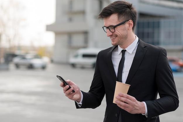 Человек с кофе проверяет мобильный