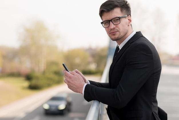 Молодой мужчина проверяет мобильный телефон