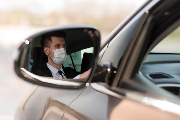マスクが付いている車の鏡の中の男