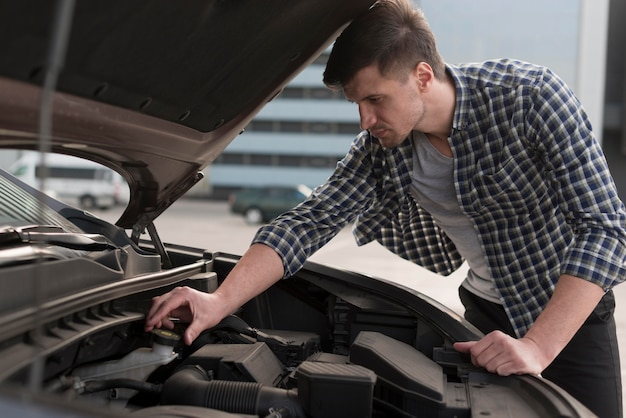 若い男が車を修正