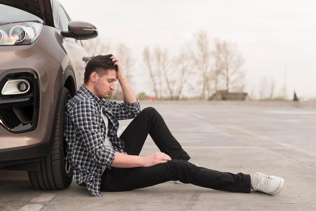 壊れた車の横に座っている動揺の男