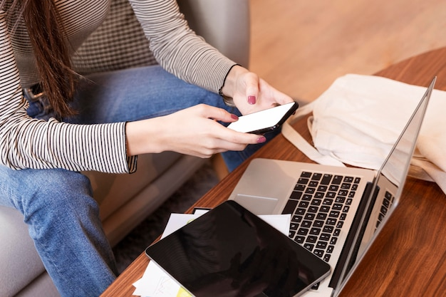 Высокий вид женщины телеработы и с помощью мобильного телефона