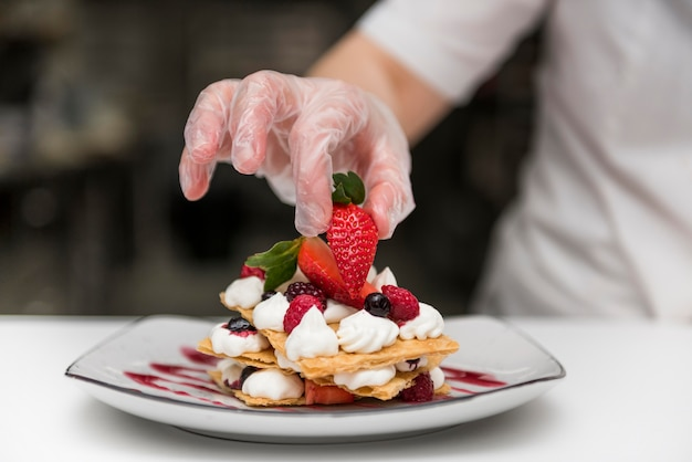 Шеф-повар кладет клубнику на десерт