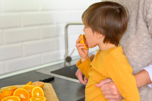 Ребенок ест оранжевый вид сбоку