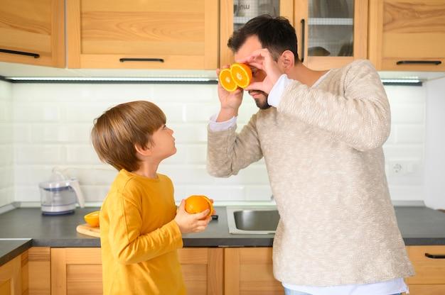 Отец и сын, держа половинки апельсинов