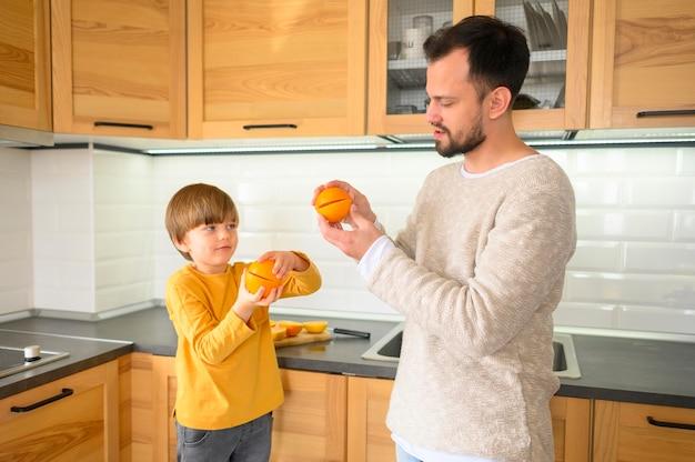 Средний снимок ребенка и отца на кухне