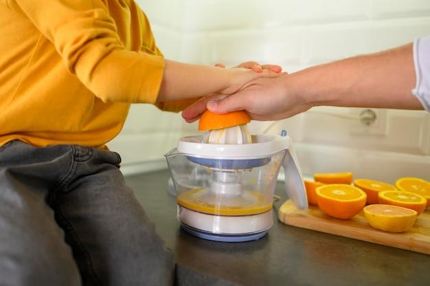 Макро отец и сын, делая апельсиновый сок