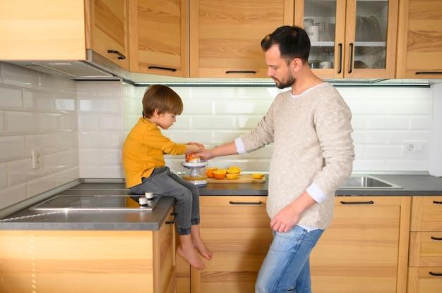 Отец и сын на кухне делают сок