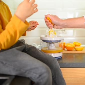 Крупным планом ребенок и родитель делает апельсиновый сок