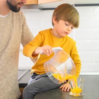 Вид спереди ребенка наливая апельсиновый сок в стакан