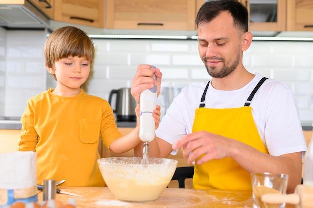 Отец и сын, делая тесто с миксером