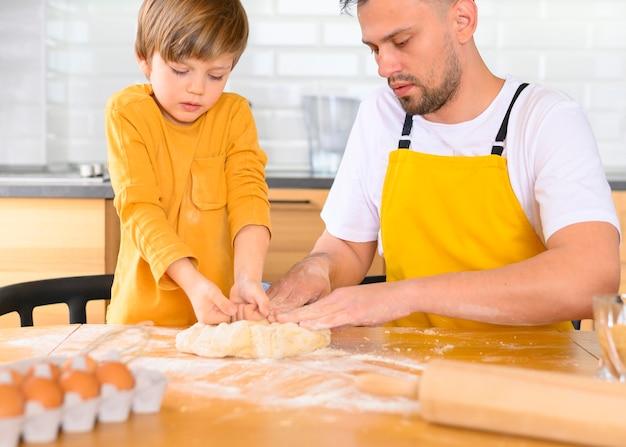 Отец и сын делают тесто на кухне