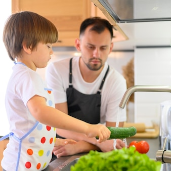 きゅうりを洗う父と息子
