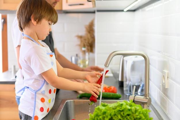 Отец и сын моют овощи