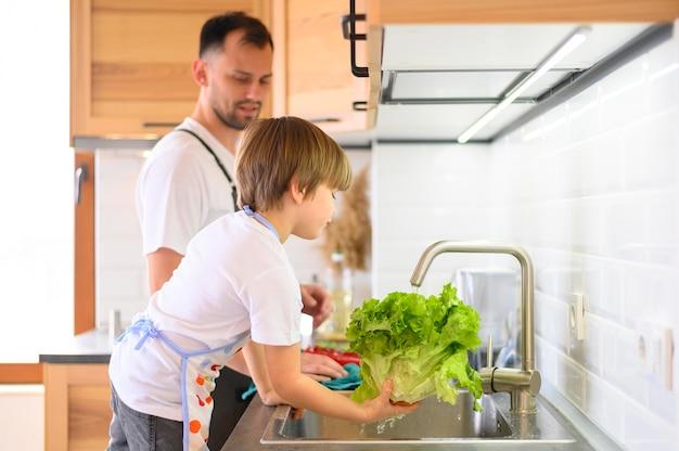父と息子がサラダを洗う