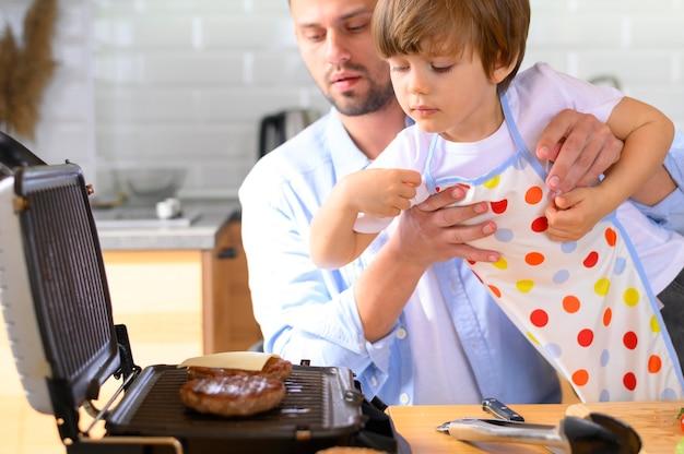 Отец с одним родителем и ребенок смотрят на гамбургеры
