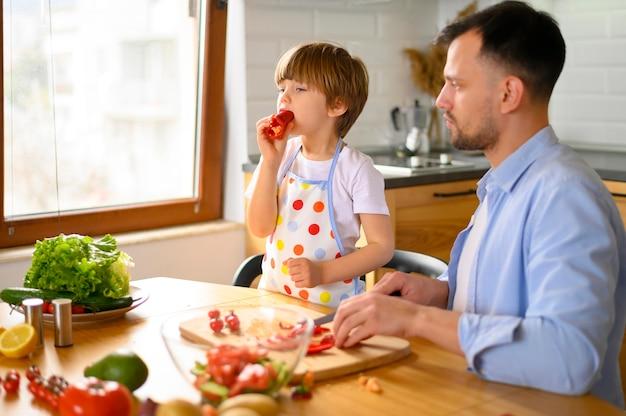 Папа и ребенок едят свежие овощи