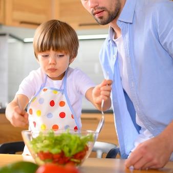 Ребенок смешивает салат из миски
