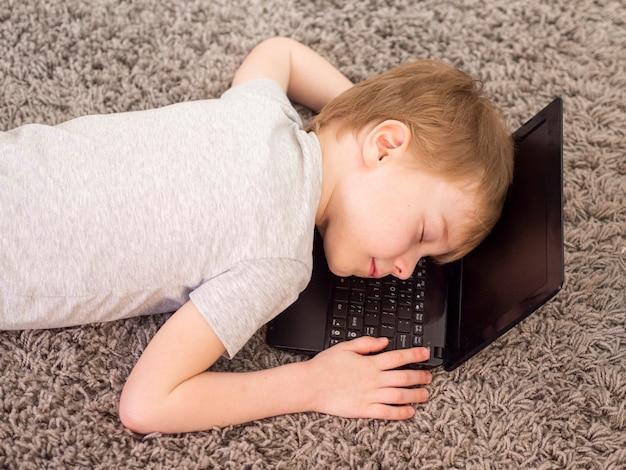 ノートパソコンで頭を横たえている子供