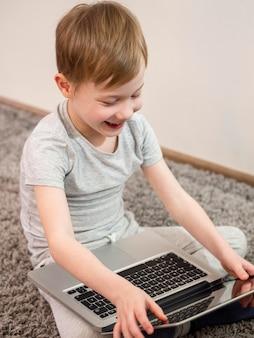 彼のラップトップで床で遊ぶ子供