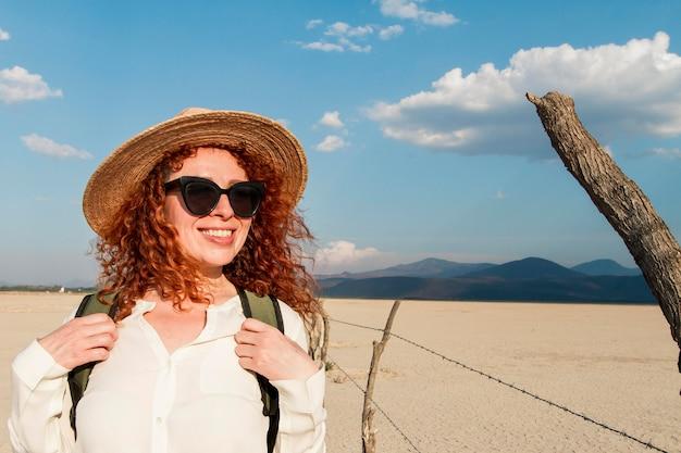 旅行の帽子を持つスマイリー女性