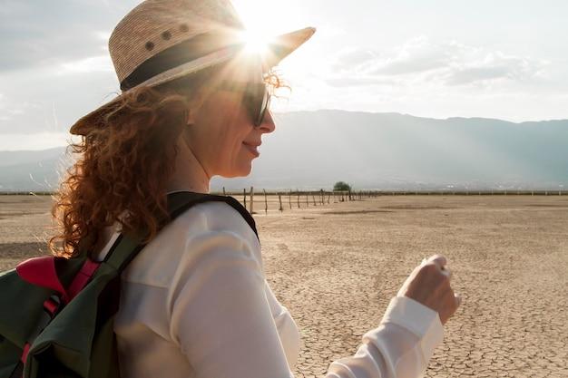旅行の帽子を持つサイドビュー女性