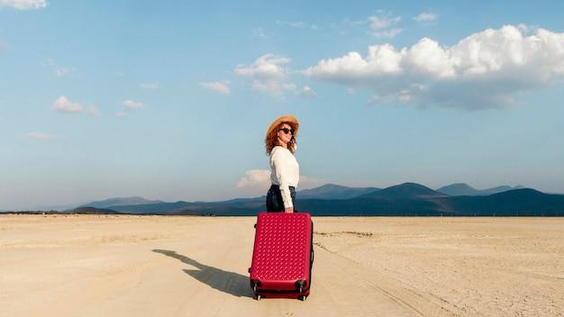 荷物を持って旅行する女性