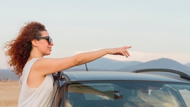 車の窓を指す女性