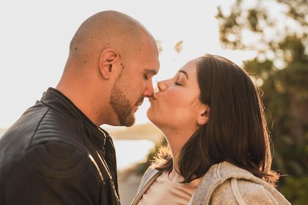 サイドビューのカップルがキス