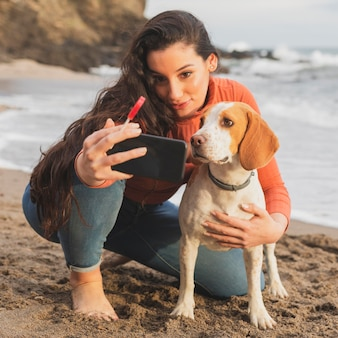 女性と犬のセルフィーを取る