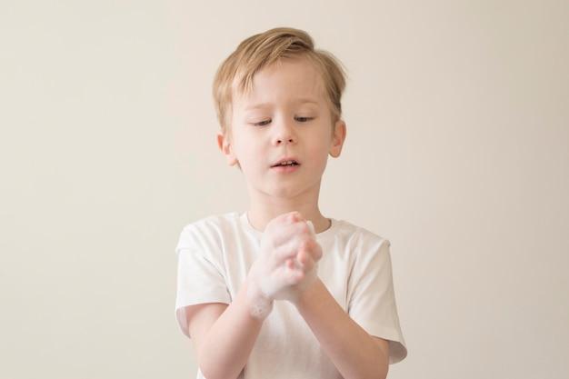 Низкий угол маленький мальчик моет руки