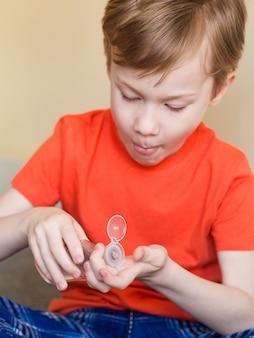 Высокий угол мальчик, используя дезинфицирующее средство для рук