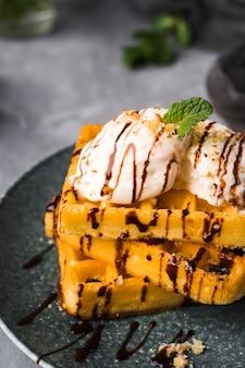 Высокий угол вафли с мороженым на тарелке