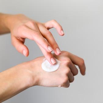 Высокий угол женщины, используя крем на руках