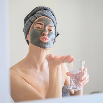 Женщина в маске для лица, дует поцелуй в зеркало