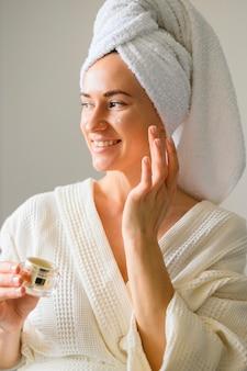 自宅で彼女の顔にクリームを適用するスマイリー女性の正面図