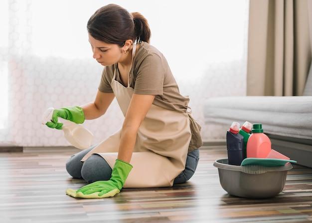 床を掃除するフルショットの女性